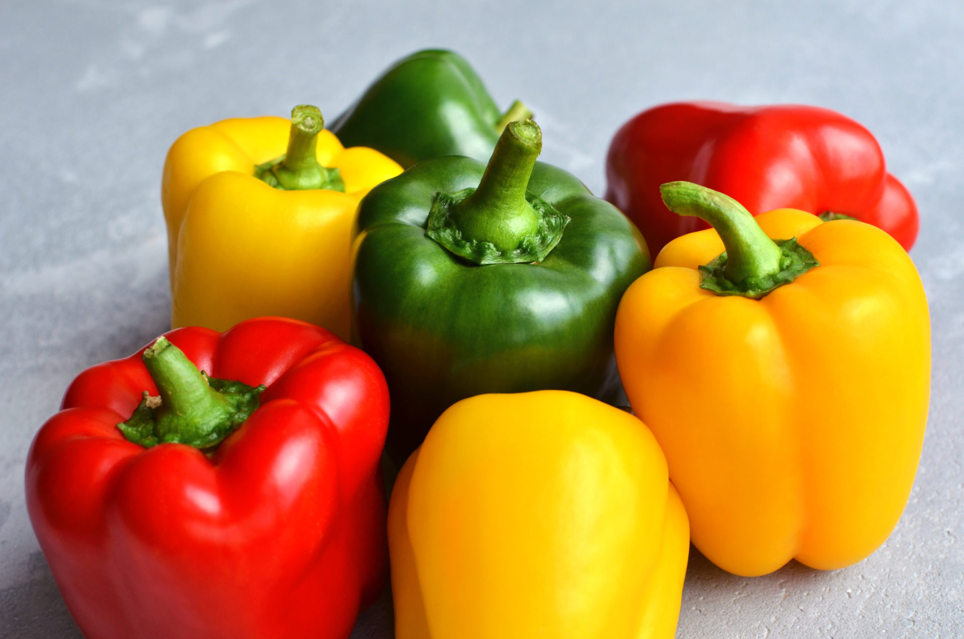 Green,,Red,And,Yellow,Bell,Pepper,On,Grey,Stone,Background.