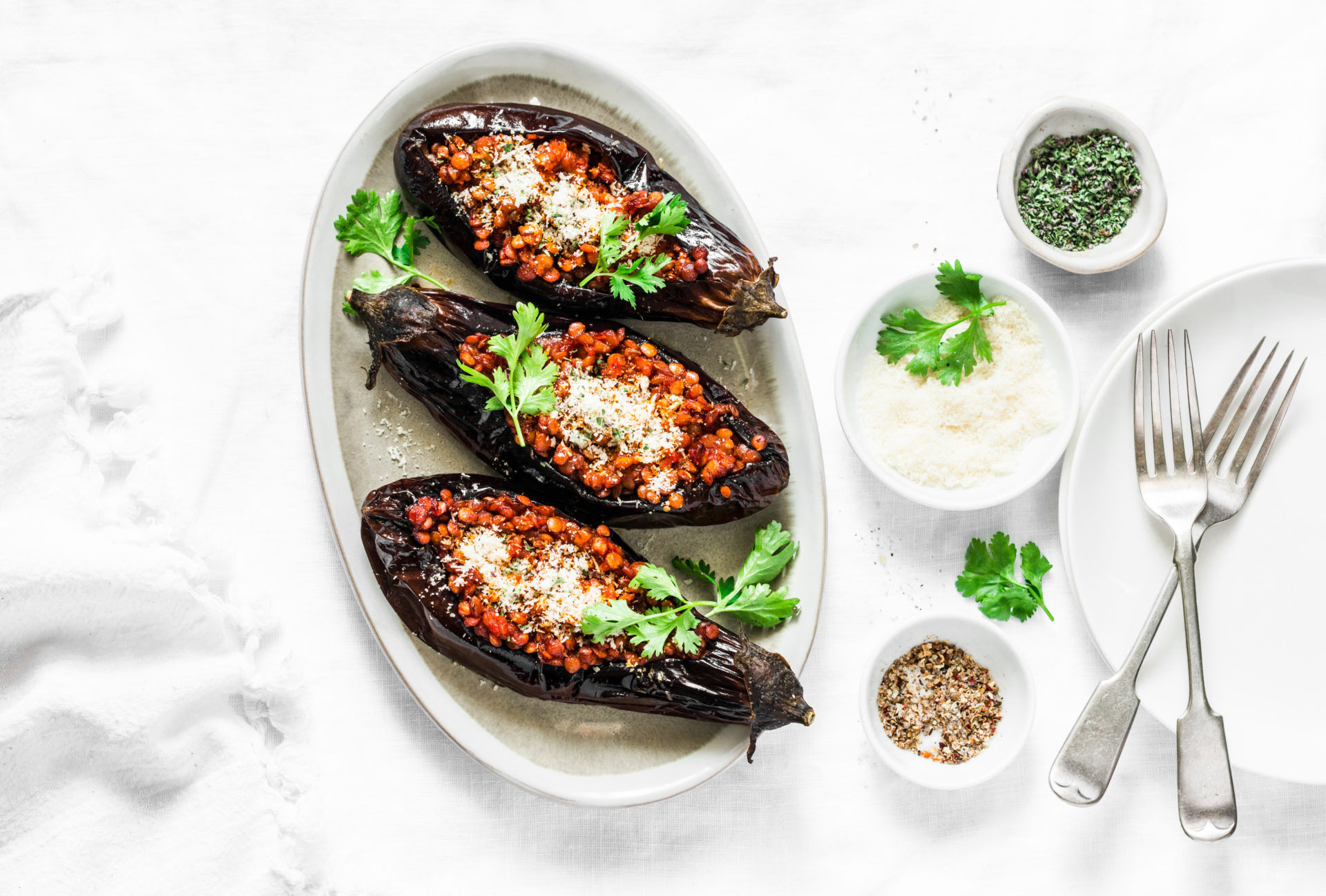 Stuffed lentils roasted eggplant - delicious healthy vegetarian served lunch  table. On a light background, top view