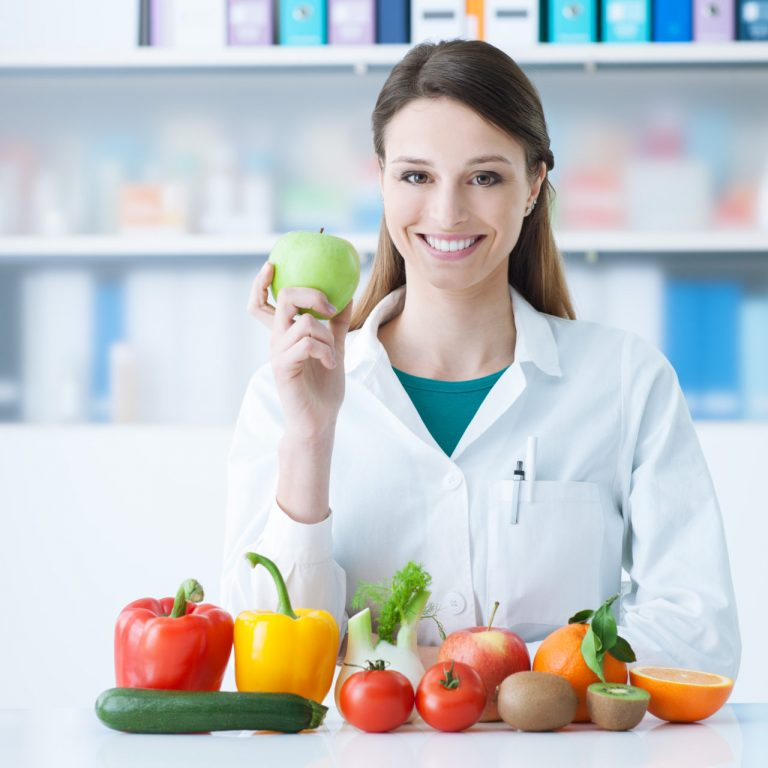 Smiling,Nutritionist,In,Her,Office,,She,Is,Holding,A,Green